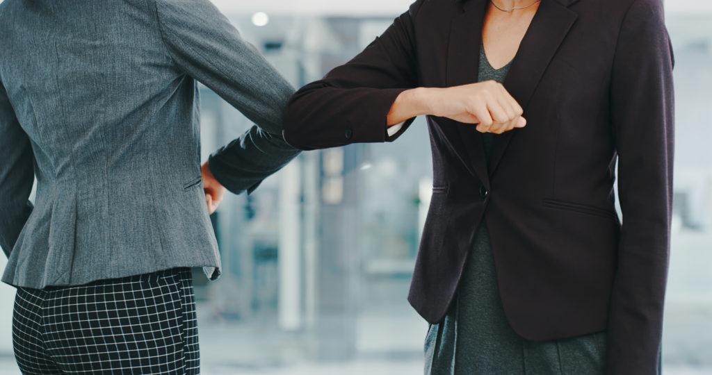 women elbow bumping