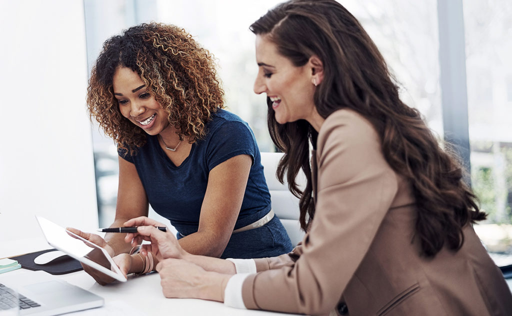 two business women collaborating on a tablet