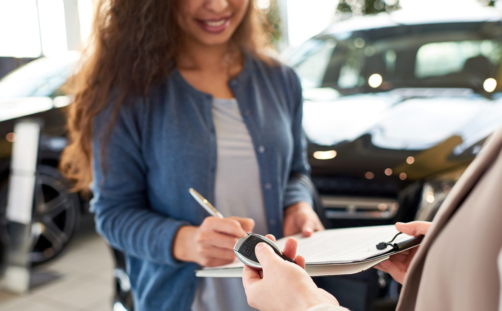 Close-up woman signing contract for new car